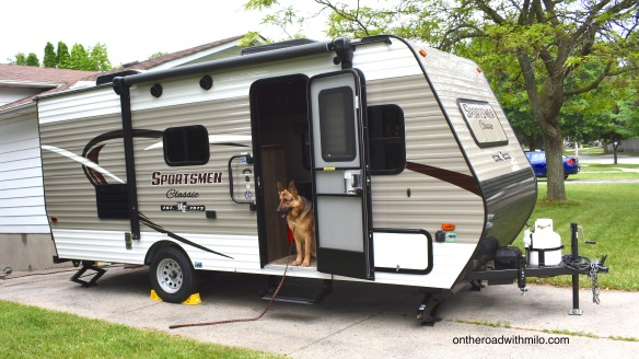 beige and white camper trailer with a black and tan german shepherd dog sitting in the doorway.