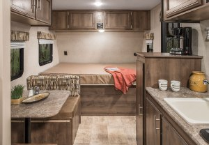 the bed, dinette, and kitchen of a camper,all in shades of brown