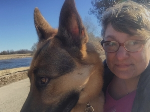 woman with short hair and german shepherd dog looking out of the picture