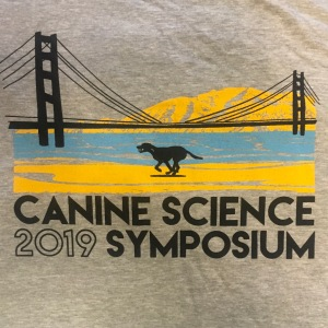 grey fabric with a cartoon image of the golden gate bridge over blue water and yellow sand with a black outline of a dog in the middle of the frame. the words 'Canine Science Symposium 2019' are printed across the bottom of the image.